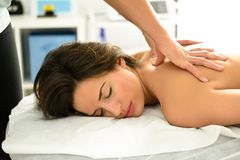 Young woman receiving a back massage in a spa center. Royalty Free Stock Photos