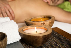 Young woman receiving a back massage in the spa salon. close-up of a candle and towels Royalty Free Stock Photos
