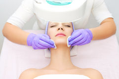 Young woman receiving beauty therapy. With cosmetologist royalty free stock image