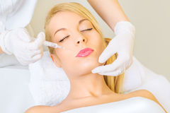 Young woman receiving botox injection Stock Image