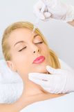 Young woman receiving botox injection in forehead Royalty Free Stock Images