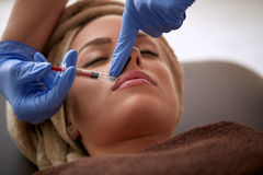 Young woman receiving a botox injection in lips Stock Photos