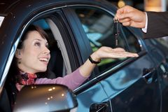 Young woman receiving the car keys Stock Photo