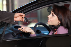 Young woman receiving the car keys from car salesman royalty free stock photos