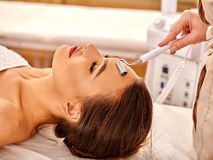 Young woman receiving electric facial massage. Royalty Free Stock Photography