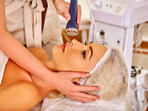 Young woman receiving electric facial massage. Royalty Free Stock Photo