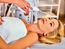 Young woman receiving electric facial massage. High frequency machine in spa salon. Young woman receiving electric darsonval facial massage after procedure at Stock Images