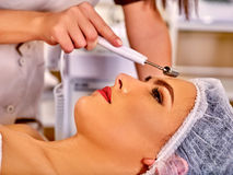 Young woman receiving electric facial massage Stock Photography