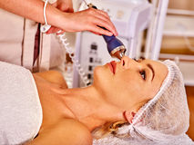 Young woman receiving electric facial massage. Stock Images