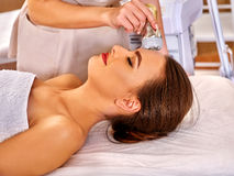 Young woman receiving electric facial massage. Royalty Free Stock Images
