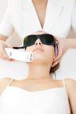 Young woman receiving epilation laser treatment stock photos