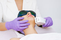 Young woman receiving epilation laser treatment. In salon Royalty Free Stock Photos