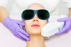 Young woman receiving epilation laser treatment. In salon Stock Image