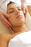 Young woman receiving face massage, eyes closed Stock Image