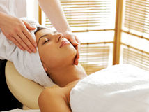 Young woman receiving facial massage, eyes closed Royalty Free Stock Image