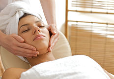 Young woman receiving facial massage, eyes closed royalty free stock photo
