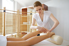 Young woman receiving foot massage from masseuse Royalty Free Stock Images