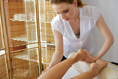 Young woman receiving foot massage from masseuse Stock Images