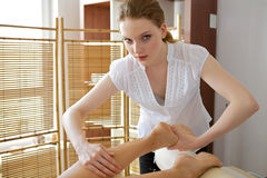 Young woman receiving foot massage from masseuse Stock Photos
