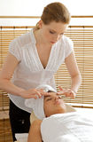 Young woman receiving head massage from masseuse Royalty Free Stock Image