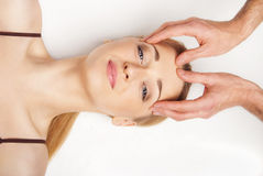 Young woman receiving a head massage on white Royalty Free Stock Photography