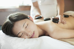 Young Woman Receiving Hot Stone Massage Stock Image