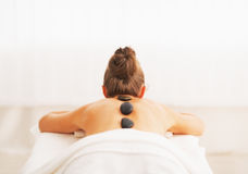 Young woman receiving hot stone massage. rear view. Young woman receiving hot stone massage in spa salon. rear view stock photo