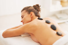 Young woman receiving hot stone massage Royalty Free Stock Photography