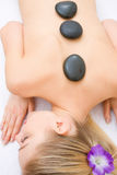 Young woman receiving hot stone treatment Stock Image