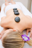 Young woman receiving hot stone treatment Stock Photos