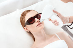 Young woman receiving laser hair removal epilation on face Stock Photo
