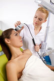 Young woman receiving laser therapy Stock Images