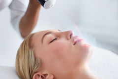 Young woman receiving local cryotherapy on her face Stock Photo