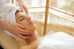 Young woman receiving massage, eyes closed royalty free stock image