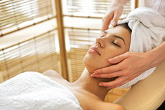 Young woman receiving massage, eyes closed. Young women receiving massage, eyes closed royalty free stock images