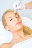 Young woman receiving microdermabrasion treatment Stock Images