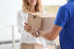 Free Young Woman Receiving Parcel From Courier Royalty Free Stock Photography - 126245317