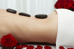 Young Woman Receiving Warm Stone Massage Red Roses Royalty Free Stock Photos