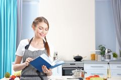 Young woman with recipe book. At kitchen Royalty Free Stock Photo