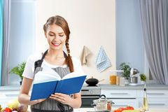 Young woman with recipe book. At kitchen Royalty Free Stock Images