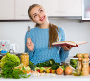 Young woman with recipe book and veggies indoors Stock Images
