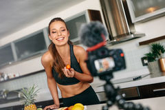 Young woman recording content for her blog in kitchen. Stock Photo