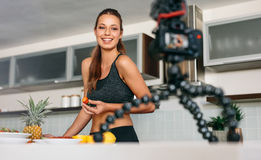 Young woman recording content for her blog in kitchen. Royalty Free Stock Images