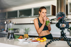 Young woman recording content for her video blog in kitchen. Royalty Free Stock Photo