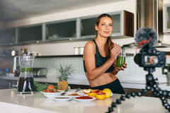 Young woman recording content for her video blog in kitchen. Royalty Free Stock Photography