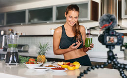 Young woman recording content for her video blog in kitchen. Stock Photos