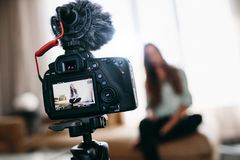 Young woman recording video for her vlog using camera with micro. Woman recording content for her vlog . Camera screen showing the woman recording her vlog Stock Photography