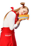 Young woman in red apron sleeping on pile of colorful tea towels Stock Photo