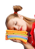 Young woman in red apron sleeping on pile of colorful tea towels Royalty Free Stock Photography