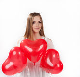 Young woman with red balloons. Young woman in white dress with   red heart shaped baloons. Valentine day concept, love concept Royalty Free Stock Image